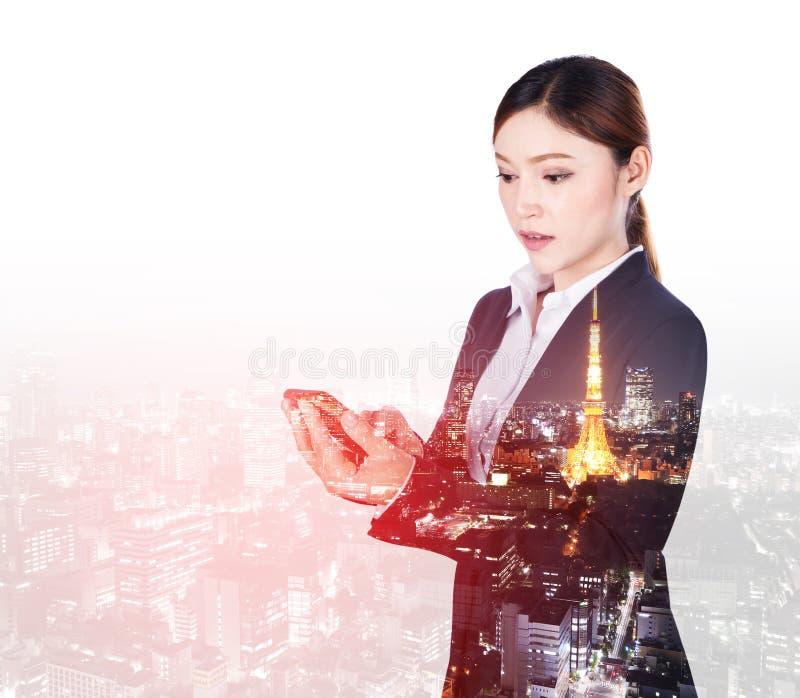 女商人两次曝光使用有城市ba的巧妙的电话 库存照片