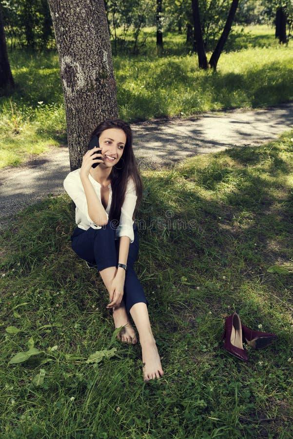 女商人休息的坐在没有鞋子的树下和谈话在电话在一个公开城市公园 库存照片