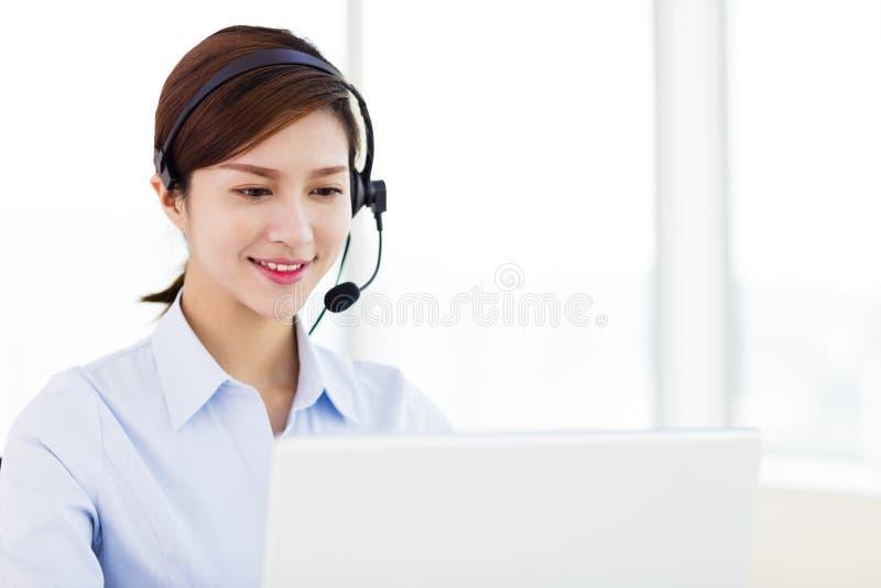 女商人佩带的耳机在办公室 库存照片