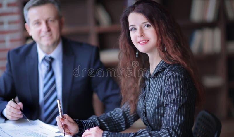 女商人和坐在书桌后的商务伙伴 免版税库存图片
