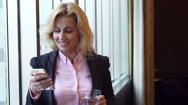女商人喝水并且看在她的电话的照片 库存图片