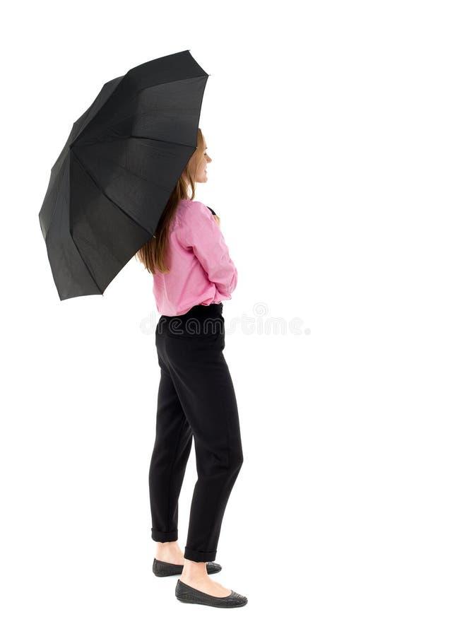 年轻女商人在伞下 库存图片