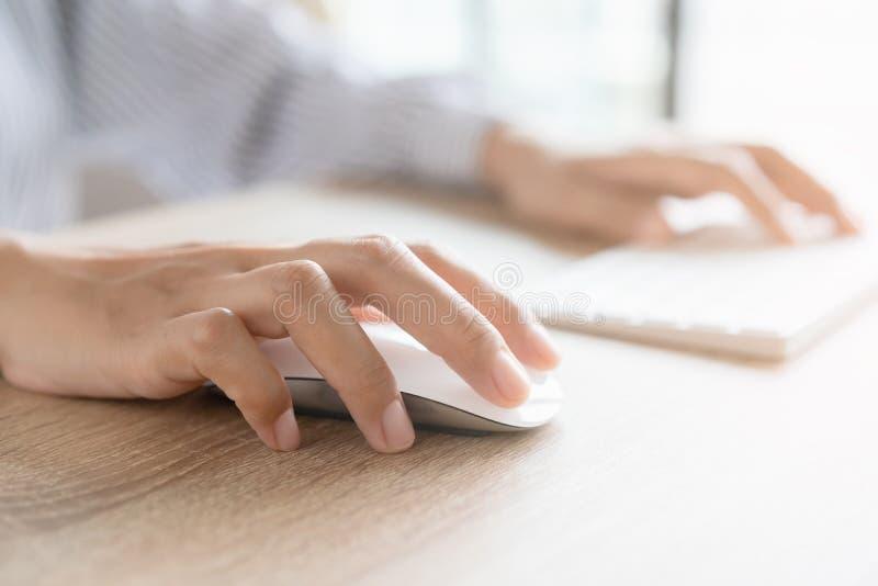 女商人在办公室或办公桌上工作时,用鼠标手敲电脑键盘的特写 免版税库存照片
