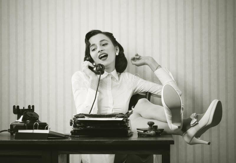 妇女谈话在电话在书桌 图库摄影