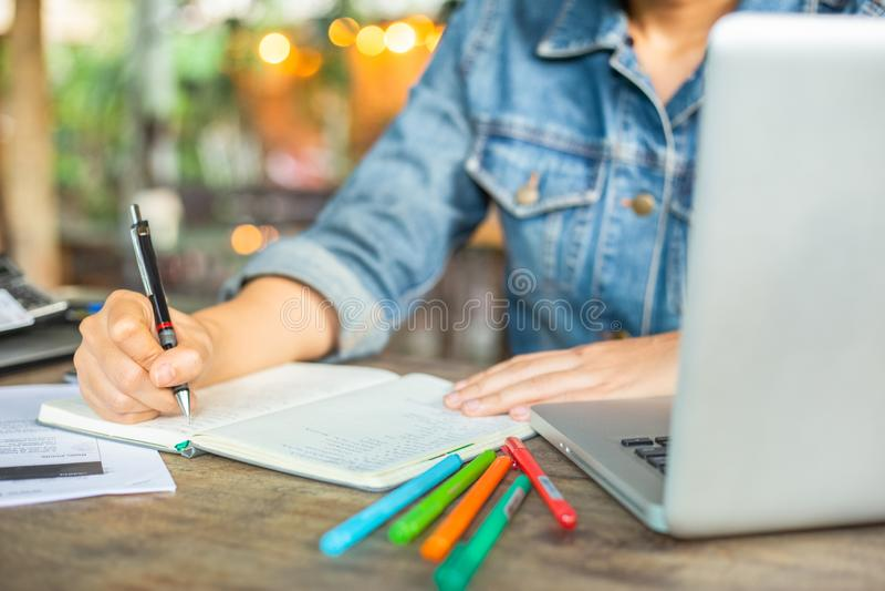 女商人在有她的计算机膝上型计算机的书桌办公室工作并且为投资写着帐户 室内设计处理 库存照片