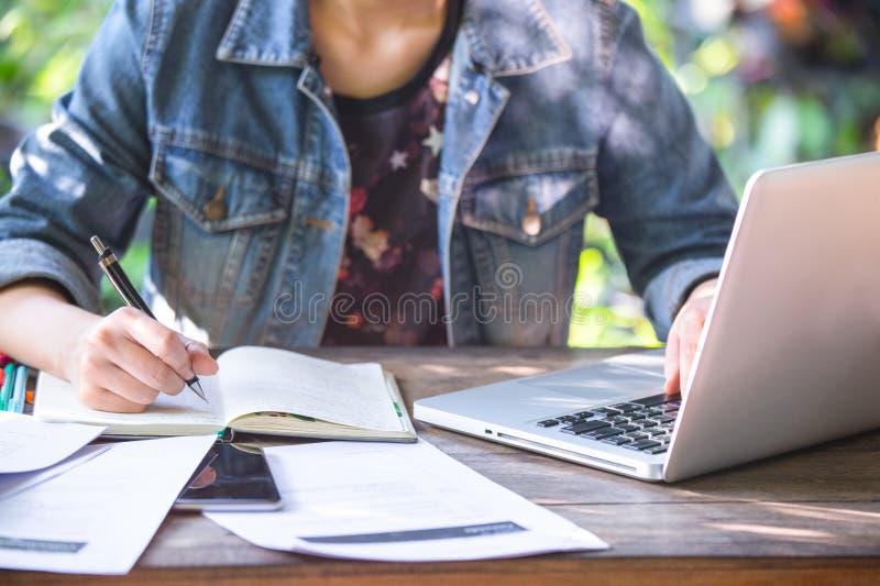 女商人在有她的计算机膝上型计算机的书桌办公室工作并且为投资写着帐户 库存图片