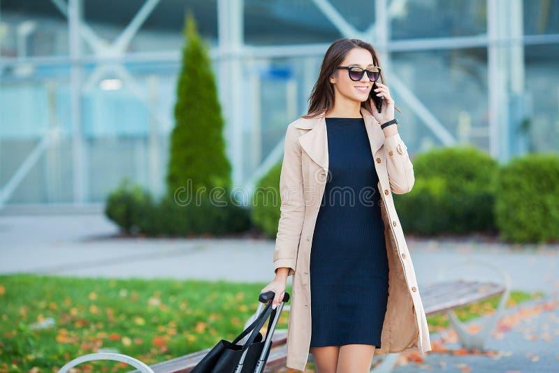 ?? 女商人在机场谈话在智能手机,当走与手提行李在去的机场装门时 库存照片