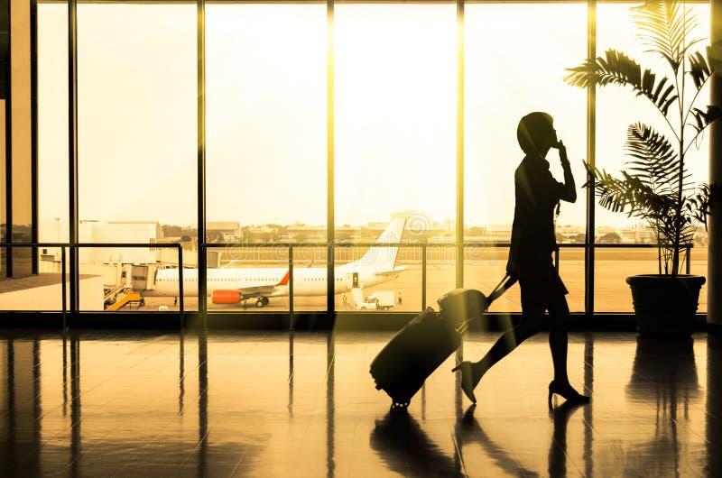 女商人在机场-乘客的剪影 免版税库存图片
