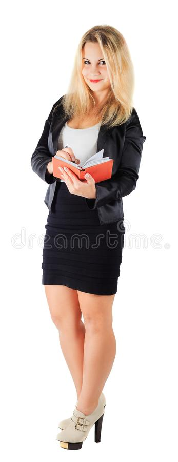女商人在橙色笔记薄写 库存照片