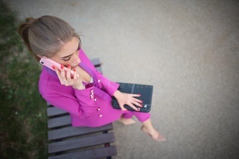 女商人坐在街道的一条长凳 免版税库存照片