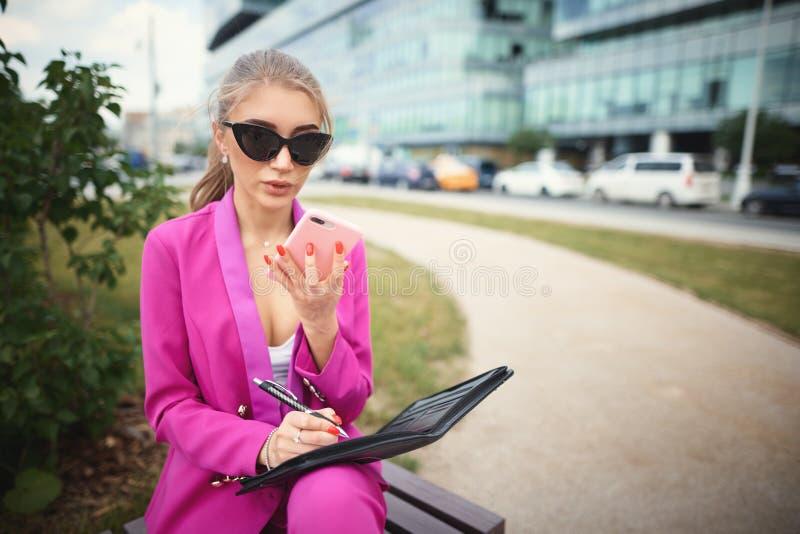 女商人坐在街道的一条长凳 库存图片