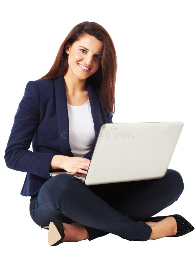 使用膝上型计算机的一名美丽的年轻女实业家的画象 免版税库存照片