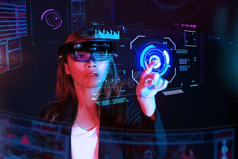 女商人尝试vr玻璃hololens在暗室|年轻亚洲女孩经验ar画象 |未来技术概念 库存照片