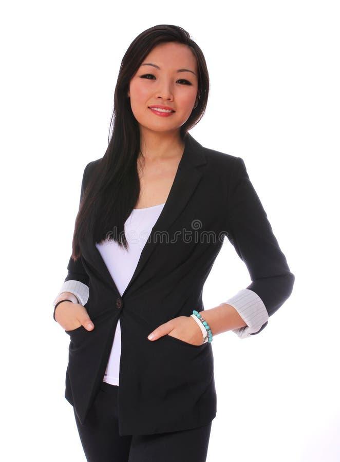女商人微笑的孤立。看照相机的黑西装的美丽的亚裔妇女 库存照片