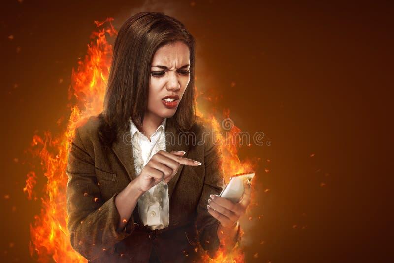 女商人恼怒的看的手机 免版税库存照片