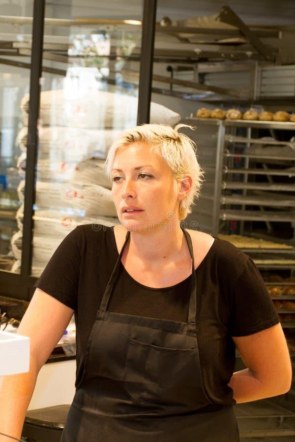 女商人所有者有面包店商店背景 免版税图库摄影