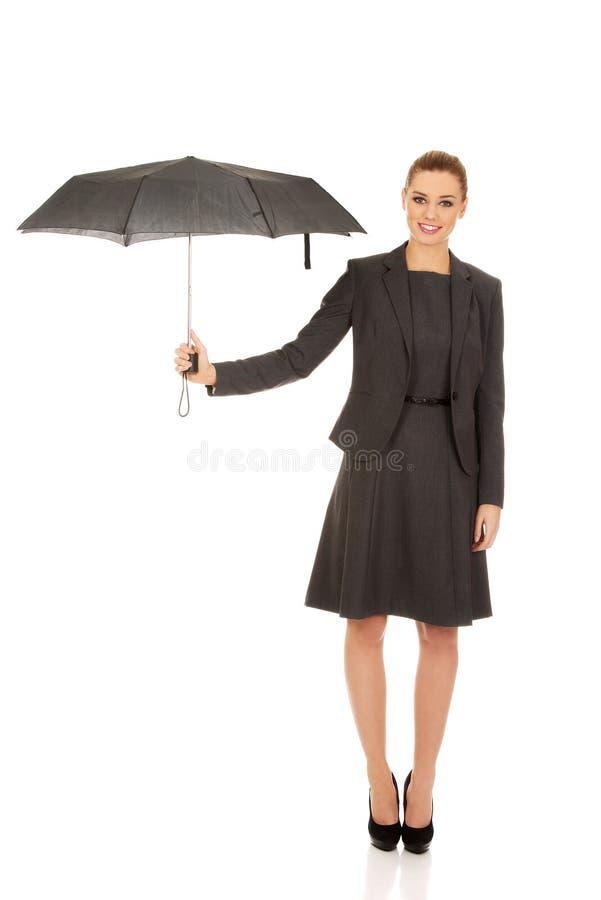 女商人拿着黑伞 免版税库存图片