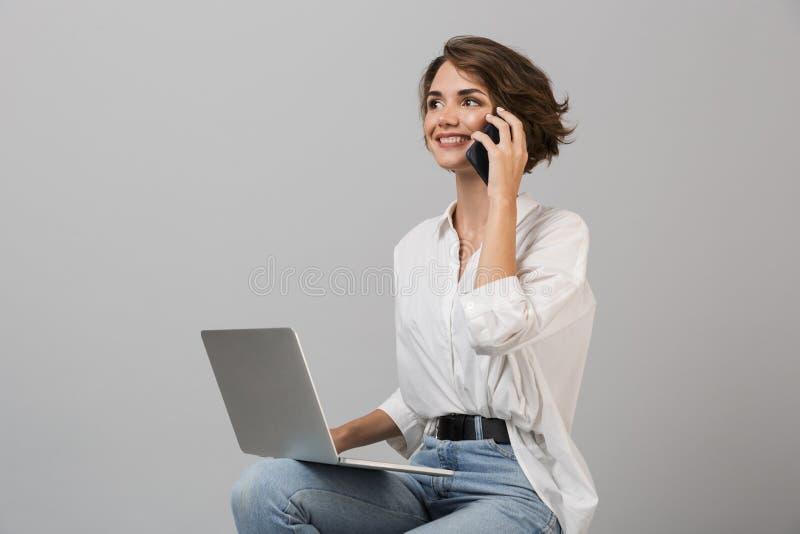 女商人摆在被隔绝在灰色墙壁背景坐凳子使用谈话的手提电脑由电话 库存照片
