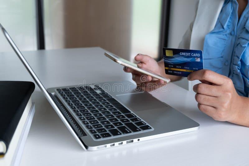 女商人消费者用途网络购物的信用卡在她的膝上型计算机和电话和付购买付款在互联网 库存照片