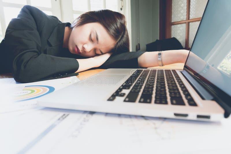 女商人疲倦了睡着在办公室屋子,当工作时 免版税库存照片