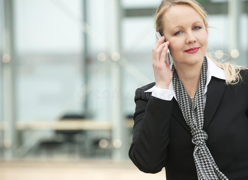 女商人的画象谈话在手机户外 免版税库存照片