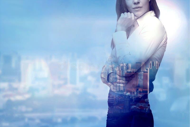 女商人考虑企业解答 在迷离的城市视图作为背景 图库摄影