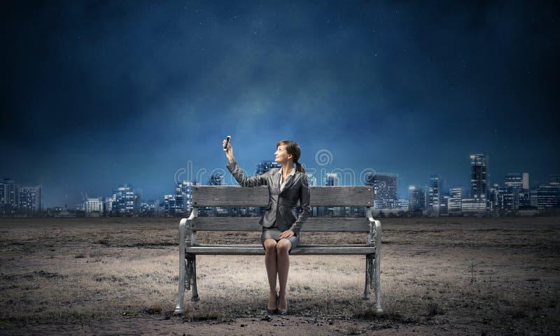 女商人藏品智能手机用被举的手 库存照片