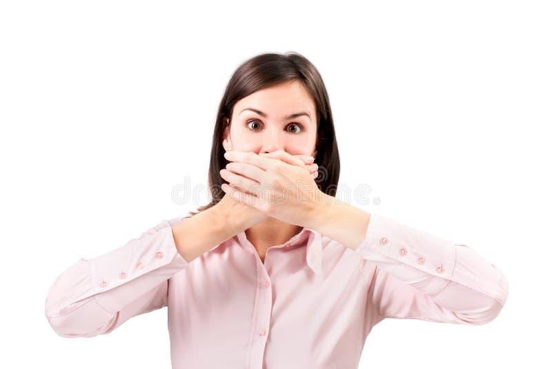 年轻女商人覆盖物用手她的嘴。 免版税图库摄影