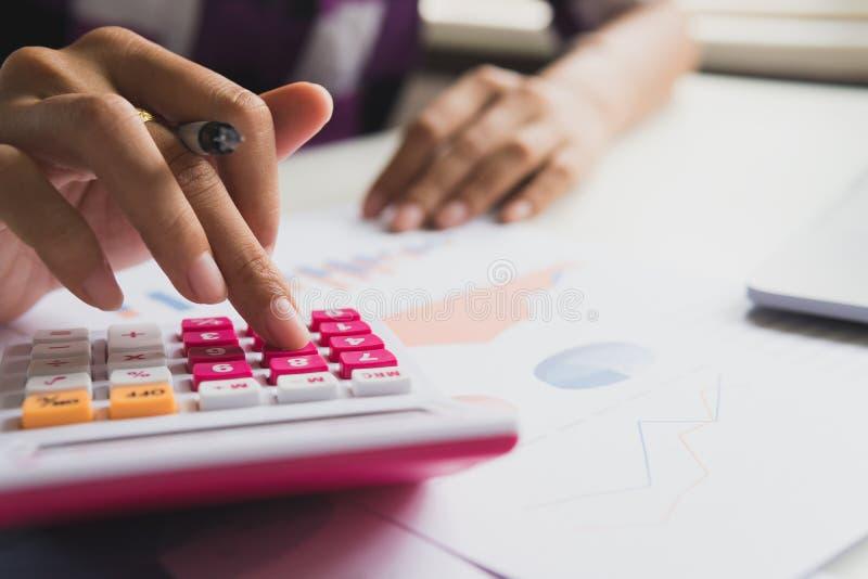 女商人计算关于费用和做财务在办公室 免版税库存图片