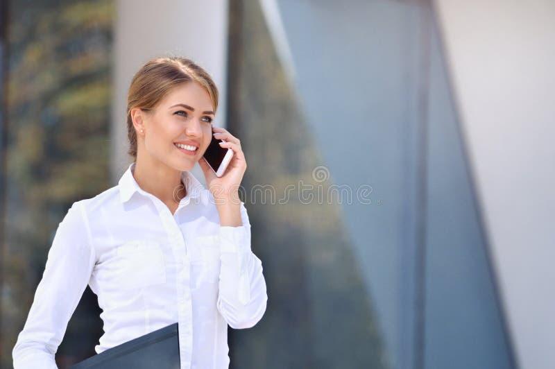 年轻女商人谈在街道上的一个手机反对大厦 库存图片