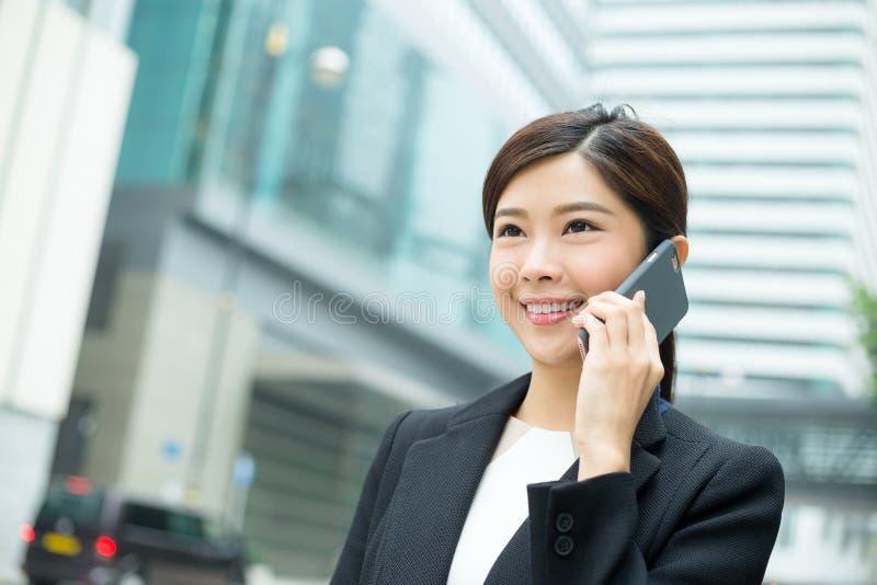女商人谈话与手机 库存图片