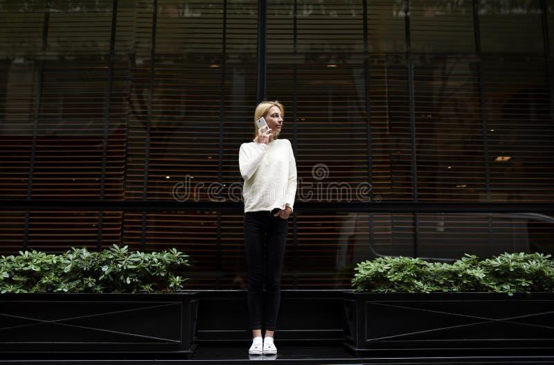 年轻女商人谈话在她的手机在城市 库存照片