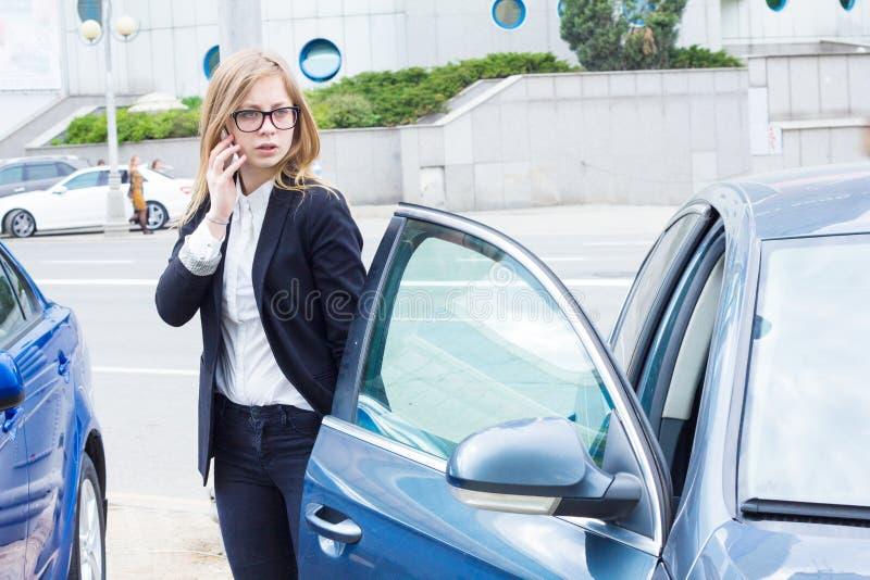 女商人谈话在电话和身分在她的汽车旁边 免版税库存图片