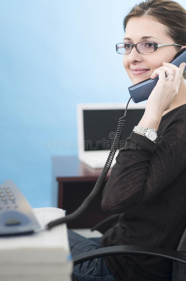 年轻女商人谈话在电话 免版税库存图片