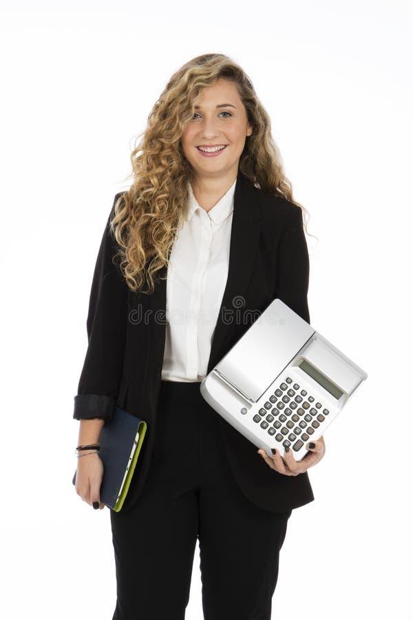 女商人身分在有计算机和现金reg的演播室 免版税图库摄影