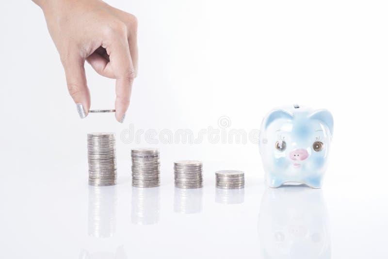 女商人递把硬币放在金钱塔和存钱罐上 库存图片