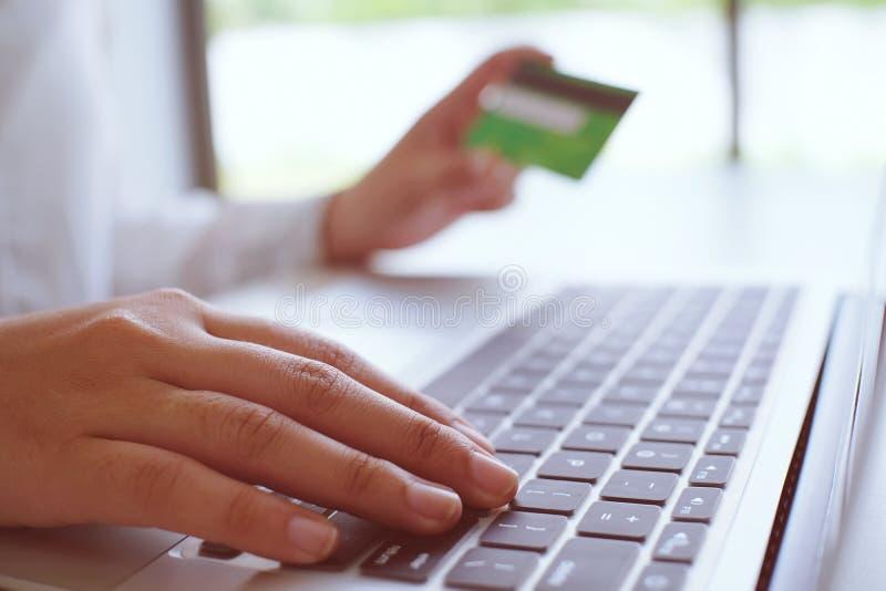 女商人递拿着塑料信用卡和使用lapto 库存照片