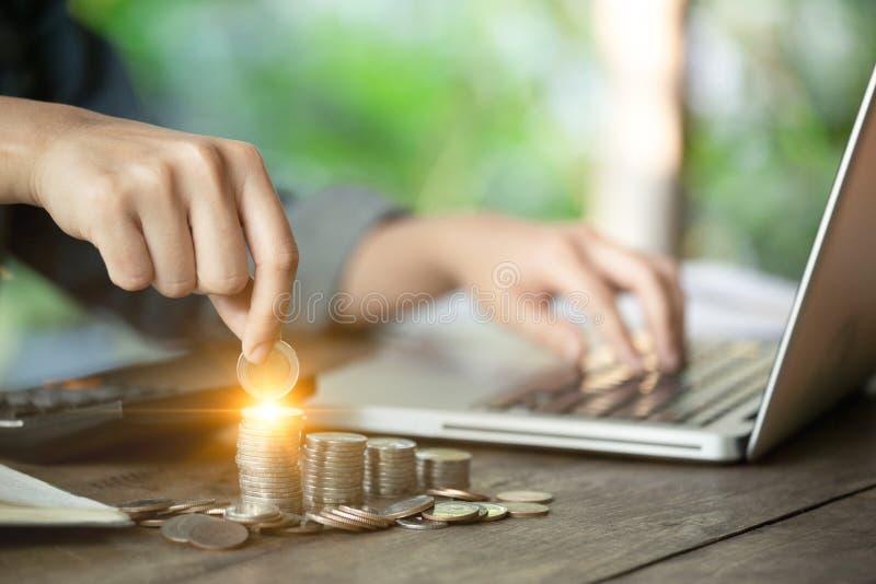 女商人递拿着攒钱概念的一枚硬币,并且与她的计算机膝上型计算机一起使用 对投资p的管理 免版税库存照片