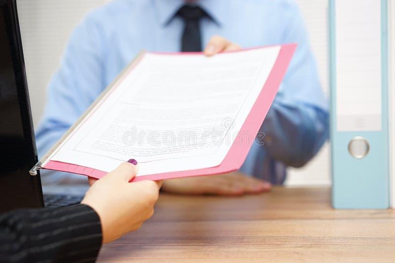 女商人通过文件给经理 免版税库存照片