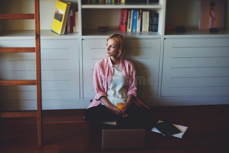 年轻女商人饮料橙汁,当食用早餐时 免版税库存照片