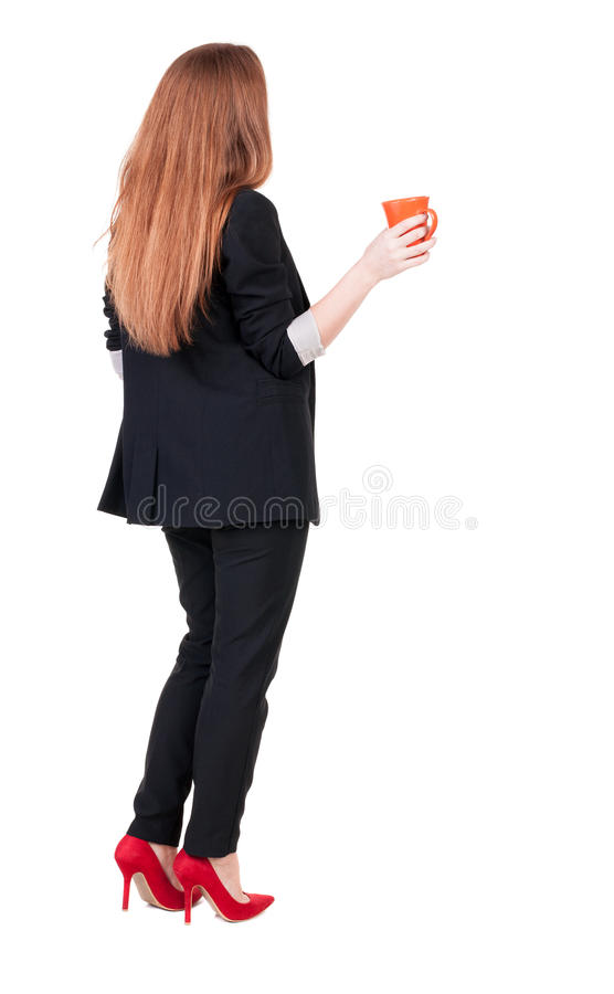 年轻女商人饮用的咖啡或茶的背面图,当时 库存图片