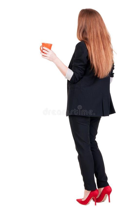 年轻女商人饮用的咖啡或茶的背面图,当时 免版税库存照片