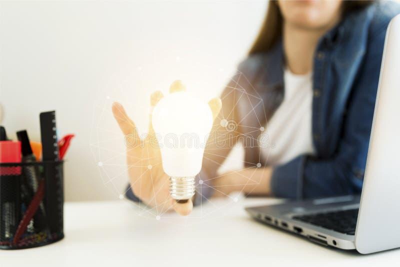 女商人` s,设计师` s新的想法的手拿着电灯泡的,概念与创新的和创造性 免版税库存图片
