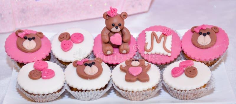 女婴与玩具熊的生日杯形蛋糕 库存图片