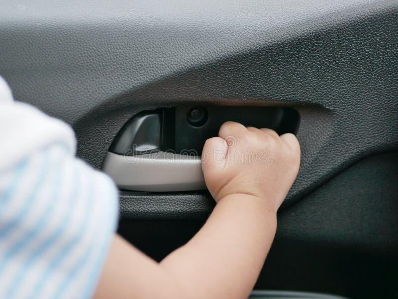 女婴从里边拉扯门把手的` s手一辆移动的汽车 库存照片