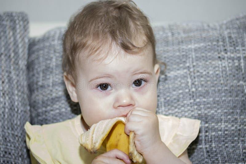 女婴吃香蕉,剥从皮肤的香蕉 一个小的女婴特写镜头的画象 孩子吃果子他自己 免版税库存图片