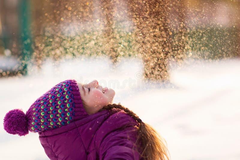 女婴在冷淡的冬天公园投掷雪 飞行雪花 晴朗的日 获得的孩子乐趣户外 免版税库存图片