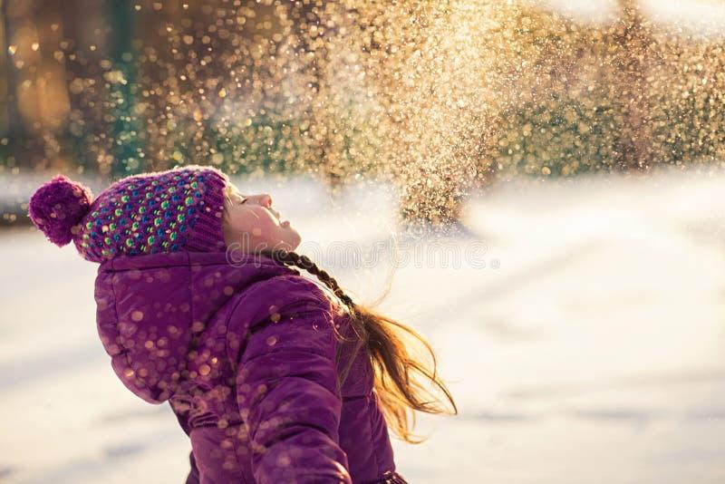 女婴在冷淡的冬天公园投掷雪 飞行雪花 晴朗的日 获得的孩子乐趣户外 图库摄影