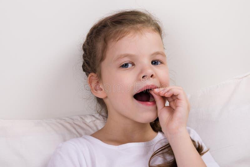 女婴在床上坐,并且检查,震动她的乳齿 库存图片