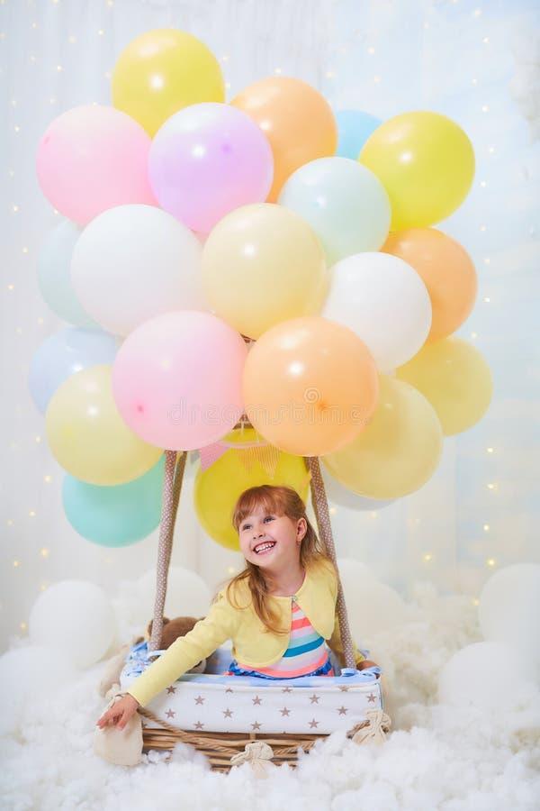 女婴坐云彩在云彩的,旅行和飞行与飞行员帽子和玻璃的气球旁边篮子 免版税库存照片